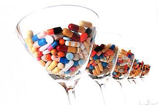 Fünf Cocktailgläser hintereinander, gefüllt mit mit bunten Arzneimitteln in Tabletten- und Kapselform.