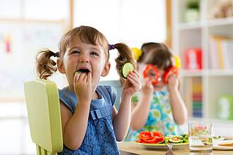 Kinder essen Gemüse und spielen damit.