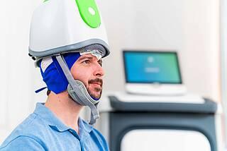 Patient mit Helm und Elektroden am Kopf bei der Magnetstimulation.