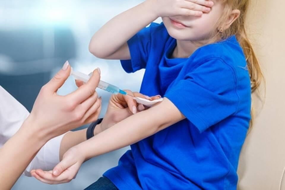 Kind bekommt Spritze in Arm und hält sich die Augen zu