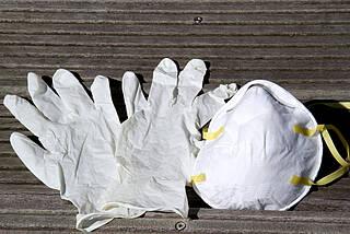 Ein Paar Einmalhandschuhe und eine Maske (beide weiß)) liegen auf grauen Holzbrettern.
