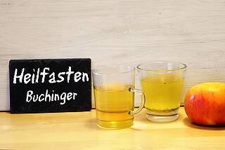 """Tisch mit Schiefertafel """"Heilfasten Buchinger"""", Gläser mit gelbem Saft/Tee, rot-gelber Apfel"""