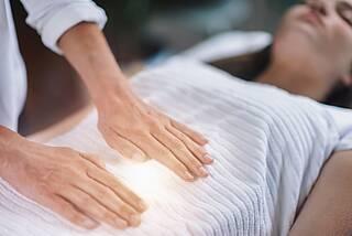 Heilpraktiker hält flache Hände über Bauch eines liegenden Patienten