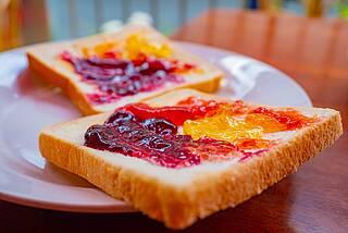 Zwei Scheiben Toast mit drei Sorten Marmelade - orange, rot, dunkelrot.