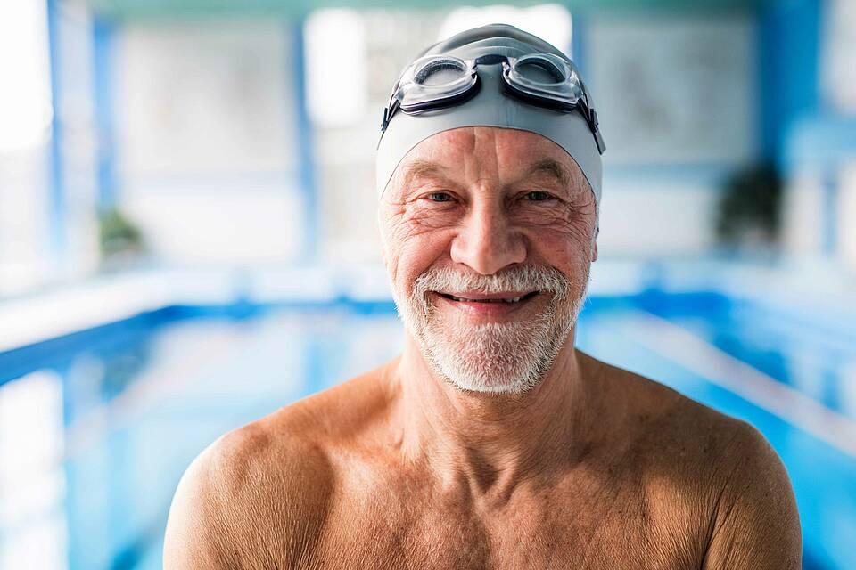 Alter Mann mit Schwimmbrille und Bademütze lächelnd am Schwimmbadrand.