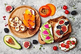 Bunte Frühstücksparade mit Frischkäsebrotscheiben mit Granatapfel, Avocado, Brombeeren, Feigen, Cherrytomaten