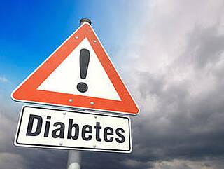 """Straßenschild mit Ausrufezeichen, darunter Extraschild """"Diabetes"""" vor Himmel mit dunklen Wolken"""