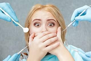Frau beim Zahnarzt hält sich Mund zu, macht große Augen vor Angst