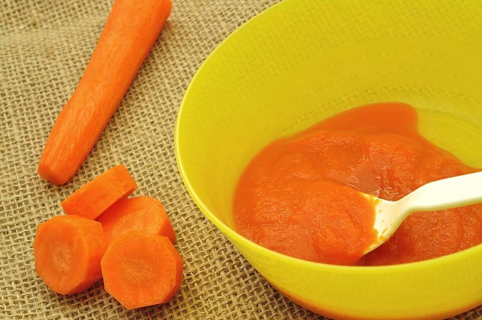 Karotten roh in Stückchen - und gekocht als Brei in gelber Schüssel.