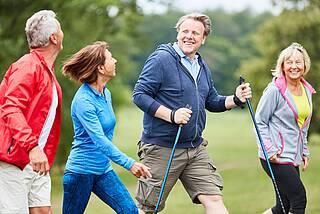 Vier Leute (m/w) über 50 beim Walking im Grünen