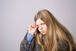 Jugendliche mit Bindehautentzündung an einem Auge
