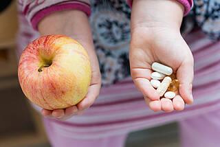 Kind mit Apfel und Vitaminpillen
