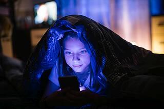 Kind Smartphone nachts im Bett, blauer Lichtschein im Gesicht