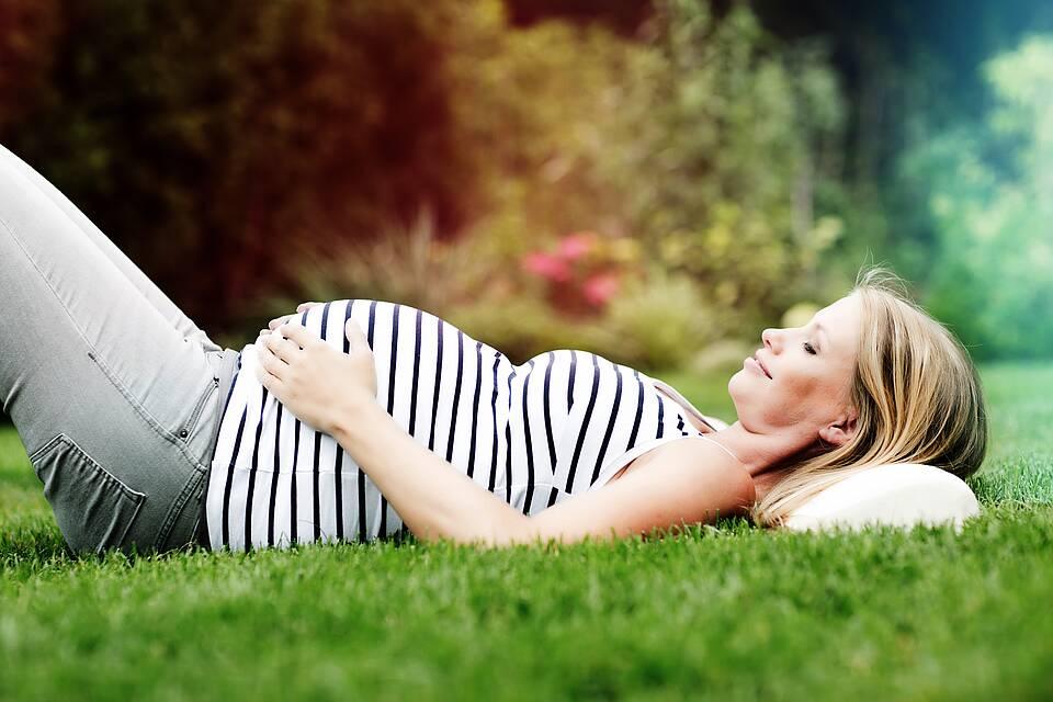 Schwangere Frau liegt auf einer grünen Wiese und hält die Hand auf ihren Bauch.