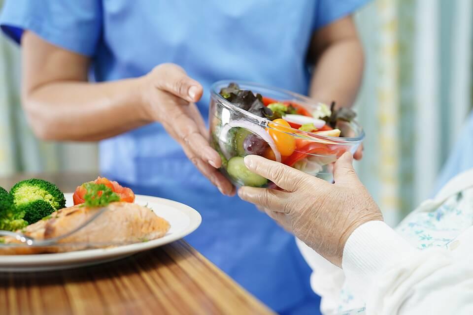 Krankenschwester reicht Patientin Glasschüssel mit frischem, buntem Salat.