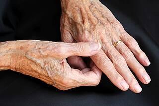 Hände eines alten Menschen, Finger berühren ein Gelenk