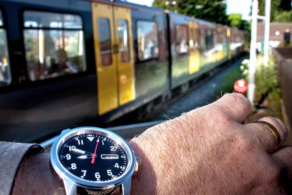 Pendler schaut auf die Uhr, Zug fährt ein.