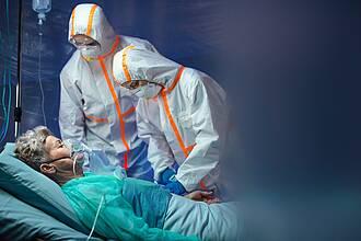 COVID-19-Patientin im Krankenhaus mit Pflegepersonal in Schutz-Overalls.