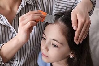 Mutter kämmt Tochter mit einem engzinkigen Spezialkamm die Haare, um Kopfläuse zu entfernen.