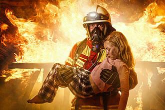 Feuerwehrmann rettet Kind aus den Flammen und trägt es auf dem Arm