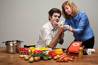 Frau verarztet Mann beim Gemüseschneiden