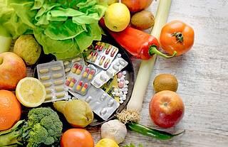 Frisches Obst und Gemüse auf Teller mit Medikamenten in Blisterverpackung
