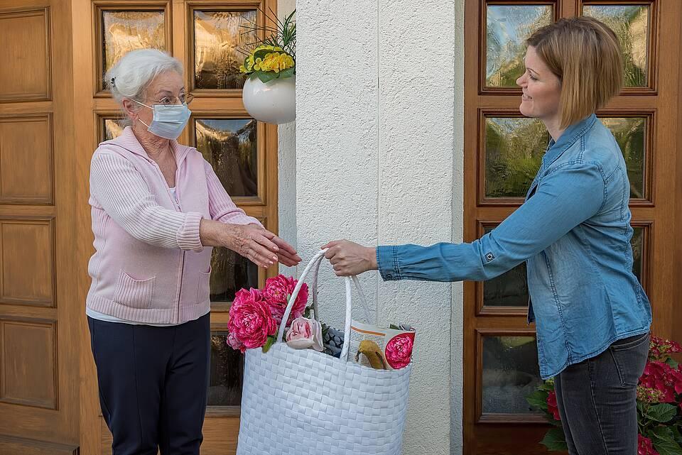 Coronakrise: Junge Frau übergibt älterer Nachbarin eine Tasche mit Einkäufen..