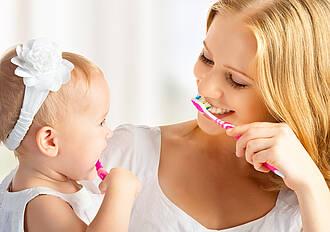 Mutter und Kind putzen Zähne