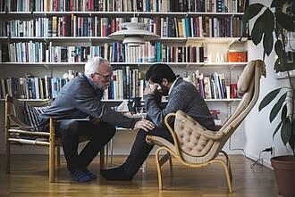 Psychotherapeut sitzt Klient gegenüber, der weint, mit Papiertaschentuch