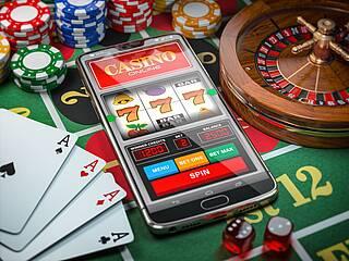 Glücksspiele - konventionell und digital: Smartphone mit Online-Casino-Spiel, Spielkarten, Roulette.