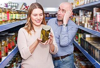 Supermarkt: Mann und Frau prüfen Lebensmittelverpackung auf Nährwertangaben