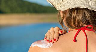 Frau cremt sich Schulter mit Sonnencreme ein