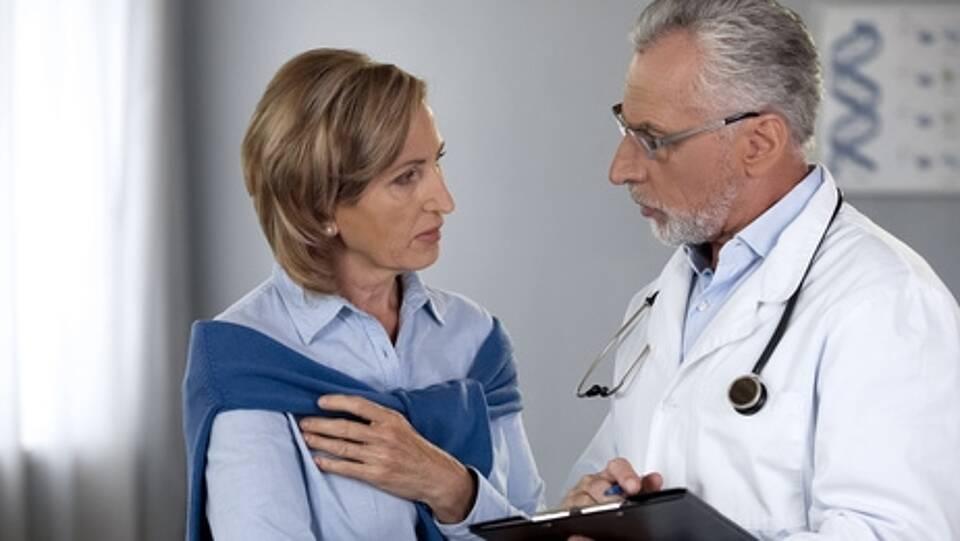Arzt mit grauem Bart und Brille im Gespräch mit Patientin