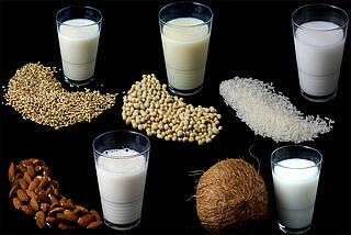Fünf Gläser mit Pflanzendrinks als Milchalternative - und fünf Rohstoffe.