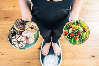 Frau in Sportkleidung auf Waage - rechte Hand: Schale mit Süßgebäck, linke Hand: Schale mit Salat.