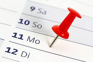 Kalender - rote Pin auf Montag gesteckt.