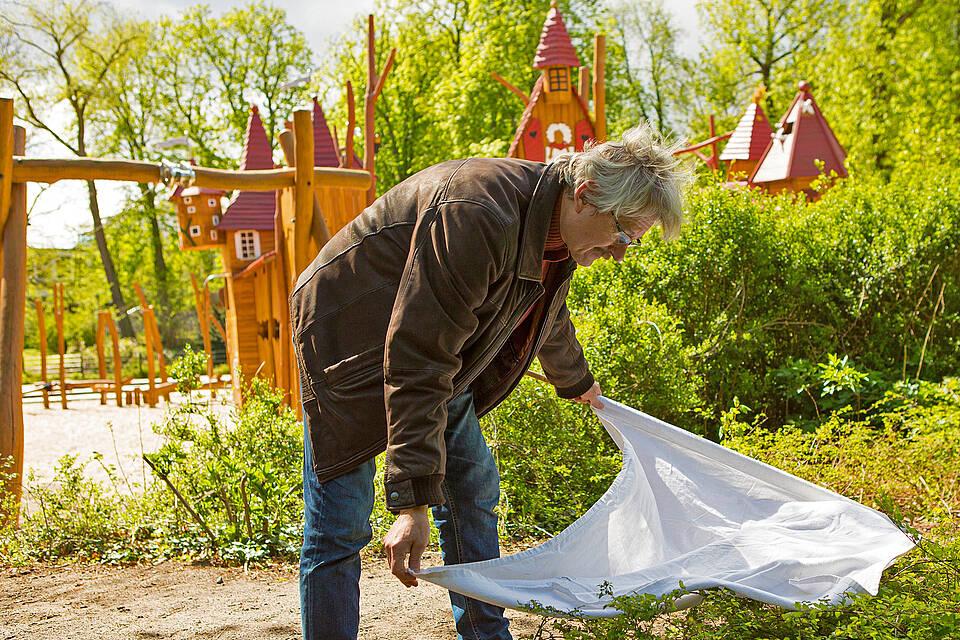 Zeckenforscher überprüft ein Gebüsch auf einem Spielplatz auf mögliche Zeckenvorkommen.