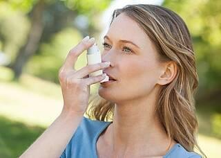 Frau verwendet Asthmaspray