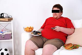 Dicker Mann sitzt auf dem Sofa vorm Fernseher mit Chips und Donuts.