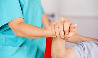 Pflegekraft hält einem Patienten die Hand.