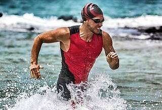 Triathlet joggt am Strand im Wasser