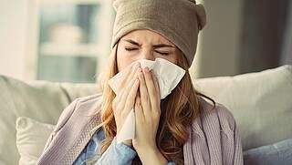 Frau mit Erkältung hält sich Taschentuch vor die Nase.