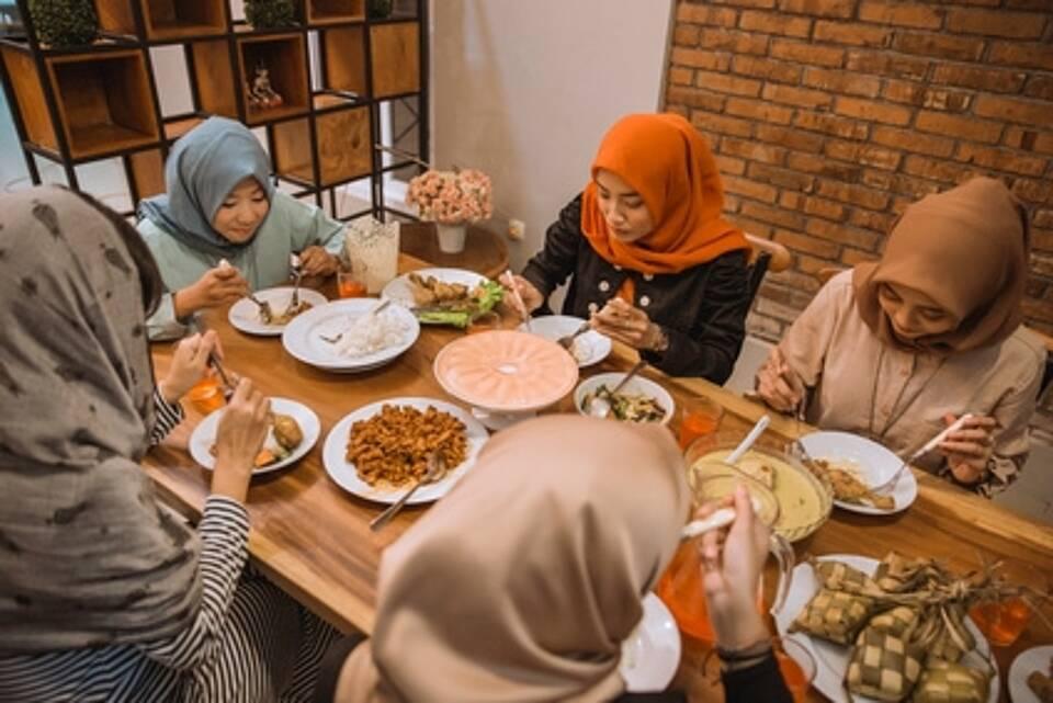 Junge muslimische Frauen mit Kopftuch beim Abendessen