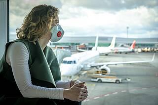 Frau mit Corona-Maske blickt am Flughafen vom Wartebereich durch die Glasfassade auf Verkehrsflugzeuge.