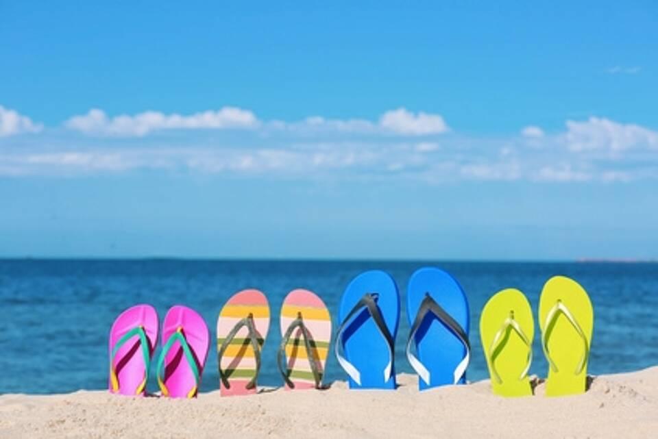 Reihe bunter Flip Flops steckt am Strand im Sand.