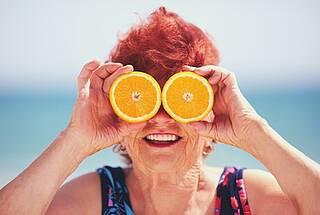 Lustige Oma mit roten Locken und Orangenscheiben vor den Augen