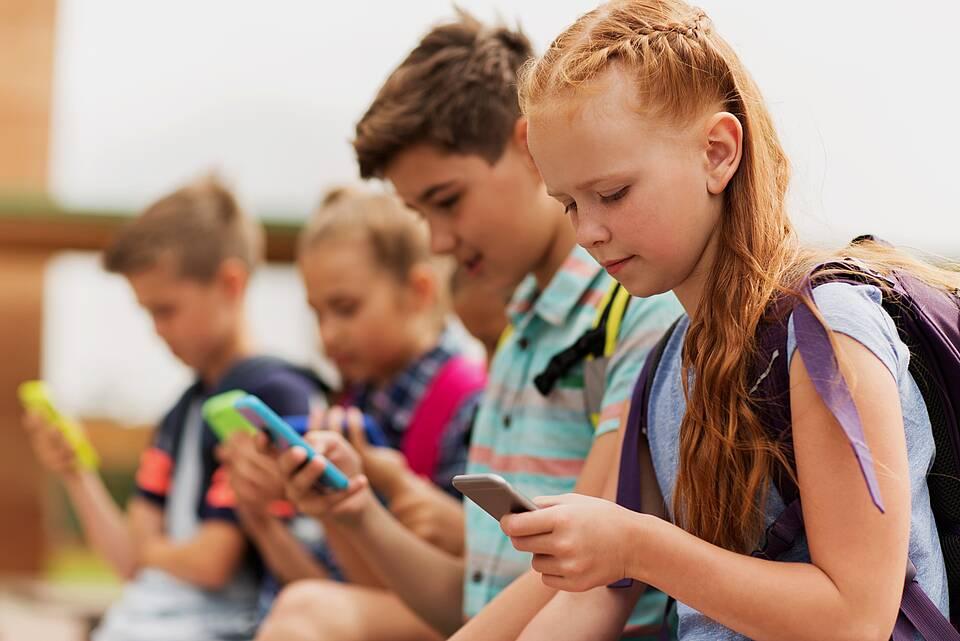 Reihe von Kindern, alle mit Smartphones in der Hand.