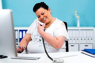 Frau mit Übergewicht fröhlich am Telefon im Büro.