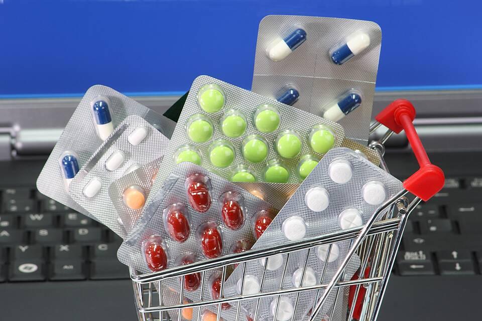 Miniatur-Einkaufswagen voller Medikamentenblister steht auf der Laptop-Tastatur.