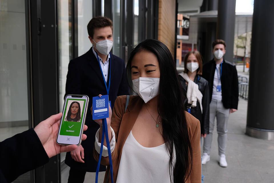 Bei einer Eingangskontrolle wird per Smartphone-Scanner der Covid-19-Gesundheitsstatus bei einer junge Frau nach Impfung oder durchgemachter Covid-19-Infektion überprüft..